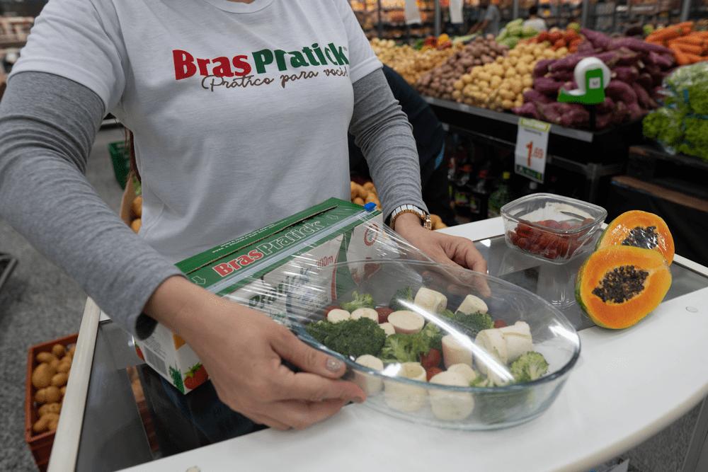 Na imagem, aparecem as mãos de uma mulher usando a caixa com cortador do filme BrasPratick para embalar uma tigela com vegetais.