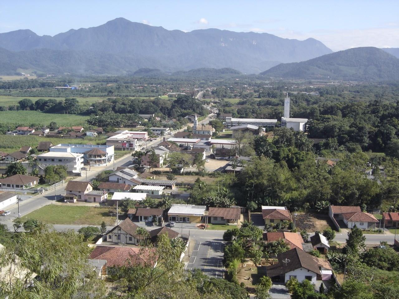 Vista aérea de Schroeder. A imagem mostra montanhas, céu azul, uma rua e várias construções rodeadas pela natureza conservada há mais de 56 anos.